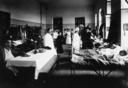 Salone adibito ad ospedale con feriti di guerra, medici, crocerossine e visitatori