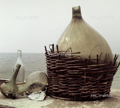 Damigiana e fiaschi di vetro abbandonati sulla riva del mare.